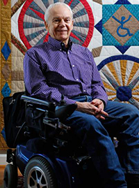 Anthony Tusler sitting in his wheelchair in front of a bright, multi-colored quilt.