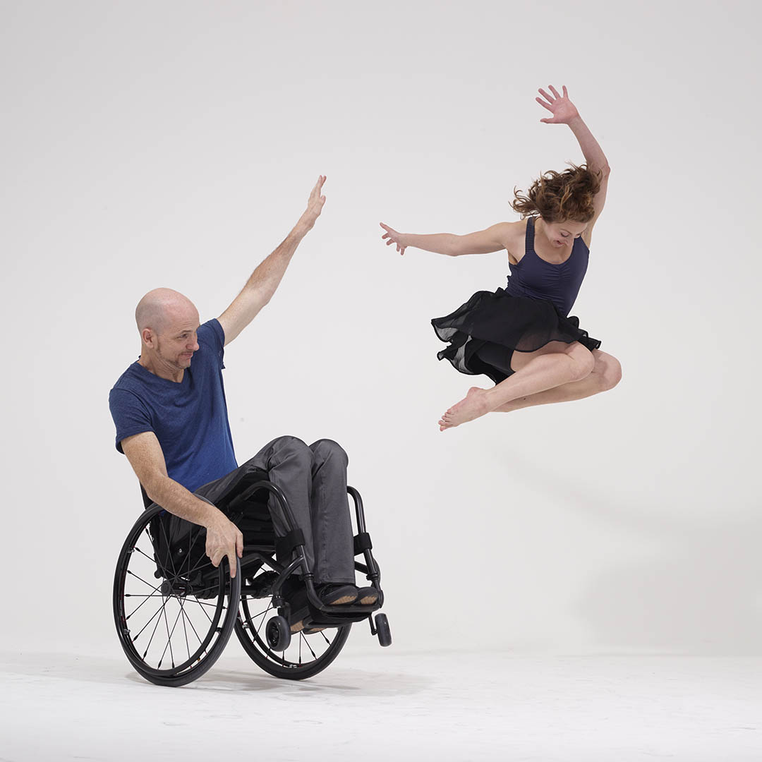 man in wheelchair in dance with woman leaping through the air