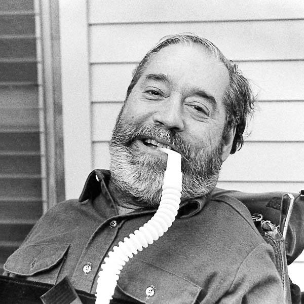 Iconic image of Ed Roberts, smiling, black and white photo, using a breathing tube