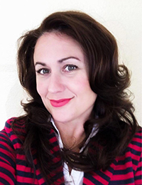 Lake Kowell's headshot, shoulder-length brown hair, striking red lips, and stripped red and blue blazer.