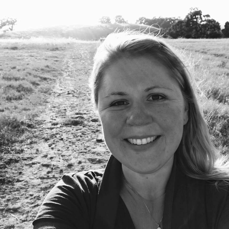 Sarah's selfie headshot, black and white photo, in the Sonoma County hills. She is smiling and has long windswept hair.