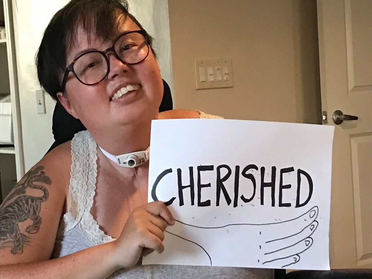"A smiling Stacey Park holding a black and white sign that says ""CHERISHED."" This image is attributed to Max Airborne."