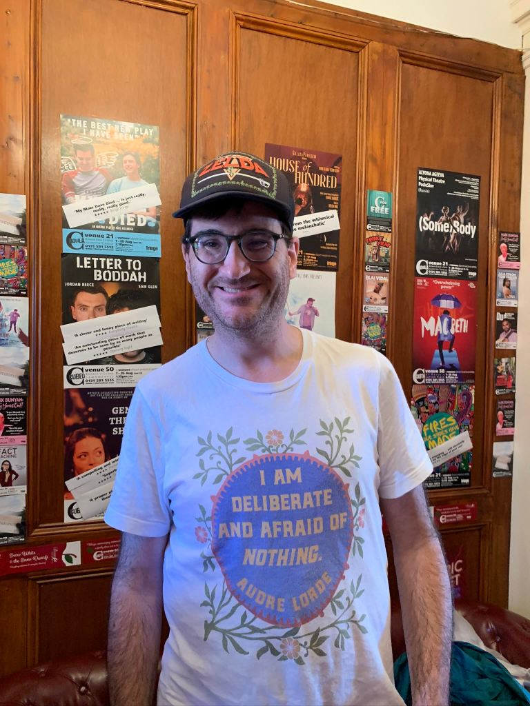 "Jae's headshot. They are wearing a shirt that says ""I am deliberate and afraid of nothing. Audre Lorde"" They are also wearing a Zelda hat and behind them are theatre posters. Jae is smiling and is wearing glasses."
